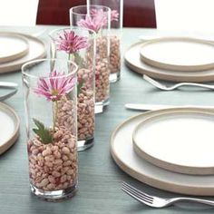 "bargain blooms: a cheap bunch of supermarket flowers, a bag of colorful dried beans and some tall glasses from your cabinet. Fill each glass with a 2- to 3-inch layer of beans and add a few tablespoons of water. Trim one flower stem to fit inside each glass, then arrange the ""vases"" down the center of the table. Bonus: After the party's over, tell guests to take these home as favors."