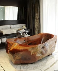 Contemporary bathroom concept with natural stone bathtub and amazing modern faucet on seamless white ceramic tiles floor