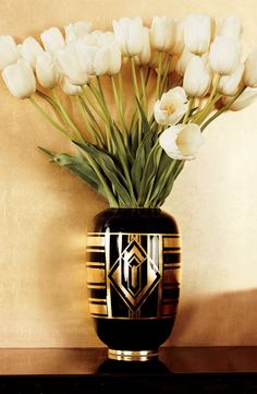 A beautiful Ralph Lauren Home art deco vase holds a bouquet of white french tulips.