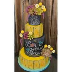Rustic Chalkboard Cake Rustic Chalkboard Cake Yellow painted aged wood paneled cake with chalkboard tiers. Hand made succulents, daisies, billy balls and lavender. Woodsy Cake, Chalkboard Cake, Succulent Wedding Cakes, Cactus Cake, Cake Central, Different Cakes, Salty Cake, Aging Wood, Colorful Plants