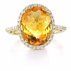 This elegant 14k yellow gold ring features 43 round brilliant cut white diamonds, of F color, VS2 clarity, of excellent cut and brilliance, weighing .49 carat total with one oval cut citrine, weighing 6.05 carats