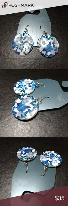 Round earrings with blue flowers These earrings are made with a shell type of material. There are pretty blue flowers on them. Jewelry Earrings