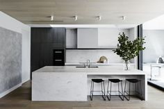 The solid stone bench grounds this kitchen, whilst the stools float beautifully in the space, tying in the black cabinetry.
