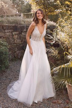 Shimmer all night in this A-line gown. The beaded bodice features an illusion plunge and a beaded motif at the waist. Illusion cutouts on the sides add modern detailing. The open back leads into a gorgeous sparkle tulle skirt. This style can come with a raised neckline option or with the front bodice lined to the side illusion inserts. It can also come in a version without sparkle tulle.