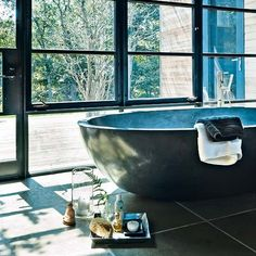 HEAVEN!!!! The bathroom is in a glazed link that connects the master bedroom with the original house. The windows open onto the deck outside, and the views beyond. This concrete bath is bespoke but the Spoon tub by Agape, available at 23 Degrees, is similar. The bath tap is by Boffi. For limestone floor tiles, try Fired Earth.