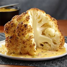 Core a whole head of cauliflower, roast and serve with a creamy, cheesy sauce for a different take on a veggie side dish.