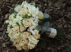 Belinda C - stunning posy of champagne and white roses and white lisianthus, finished off with soft gum and white and pewter ribbon wraps accented with pearl pins