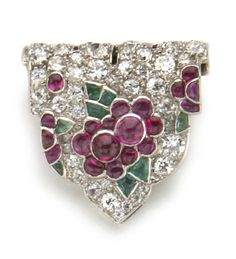 An art deco tutti frutti diamond and gem-set clip brooch, French, Cartier, circa 1925  in the form of a shield, pavé-set with old European-cut diamonds and accented with cabochon ruby and emerald flower detail; signed Cartier, Paris; with French assay marks; estimated total diamond weight: 1.50 carats; mounted in platinum and eighteen karat white gold.