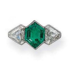 A THREE-STONE EMERALD AND DIAMOND RING   The hexagonal-shaped emerald flanked by two shield-shaped diamonds