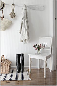 Something sweet and scandinavian:) about this entryway… Fresh and clean.. Love the whites http://fengshui.about.com/od/fengshuiuseofcolors/qt/fengshuiwhite.htm and the simplicity of panelled wall and simple striped rug. May not be  very practical but can work if you are single :)