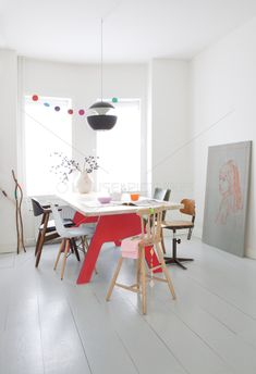 Fantastic dining room with white-painted floor and red trestle-style table.