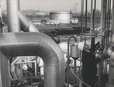Stabilimento di Bovisa. Primo piano di un tecnico al lavoro sull'impianto UGI per la produzione di gas da reforming di D.L.P.: sullo sfondo un serbatoio da 7000 mc per lo stoccaggio di D.L.P - 1968