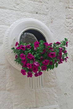 tire planter painted white and hung on white wall holding large bunch of flowers. Fun and creative collection of 29 flower tire planter ideas for your yard, patio or walkway. Splash some color in your yard with these creative ideas.