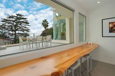 How cool is this? A natural wood plank counter positioned beneath an expansive single-track sliding window system, allowing you to enjoy the views and fresh air while eating your breakfast.