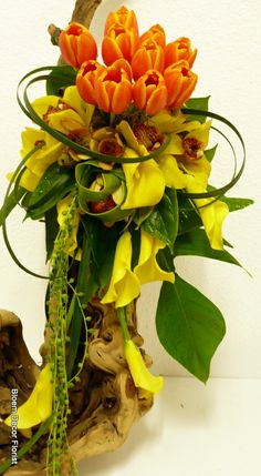 Modern, unique bride's bouquet with orange tulips, yellow cymbidium orchids, yellow calla lilies, lily grass, split aspidistra leaves, lemon leaf and Sting of Pearls succulents.