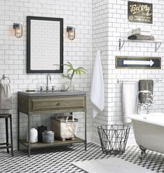 Vintage inspired bathroom with black and white geometric tile floor and floor to ceiling white subway tile.