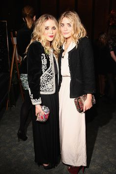 The Olsen twins add a pop of color to their black and white outfits with patterned and bright colored clutches. via StyleList