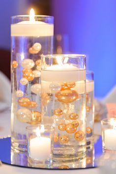 Floating Candle Centerpieces With Gold and White water beads and mirror underneath