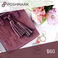 """Burgundy Tassle Handbag Adorable burgundy tassel handbag. Soft suede feel! Size: 7.5""""L x 7.5""""W x 3""""D. 2 interior pockets, double tassel accents. Note this is a boutique handbag, no brand or tags but it is brand new 💕 mini sized for easy travel to fit your essentials!  - 2 wear options: 25"""" adjustable shoulder strap drop length 3"""" double handle drop length Bags Crossbody Bags"""
