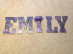 wooden letters painted black with metallic purple zebra stripes and Cricut embellishments!