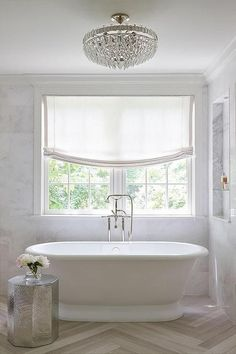 Sophisticated, elegant bathroom features a crystal semi flush mount hanging over an oval freestanding tub and floor mount tub filler placed under windows dressed in one white roman shade and a marble…More Bathroom Window Treatments, Bathroom Windows, Bathroom Renos, Bathroom Ideas, Bath Window, Bathroom Goals, Window Blinds, Bathroom Spa, Curtains For Bathroom Window