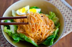 bibimguksu is a korean cold noodle dish with different kinds of stir-fried or fresh vegetables with a spicy gochujang sauce.