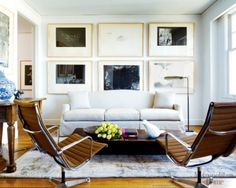 Sleek, modern chairs paired with classic couch...cool framed art arrangement