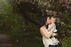 Spring photos, cherry blossoms raining on Mom kissing little girl Mommy and Me with the Cherry Blossom Tree-Edmonton Family Photographer
