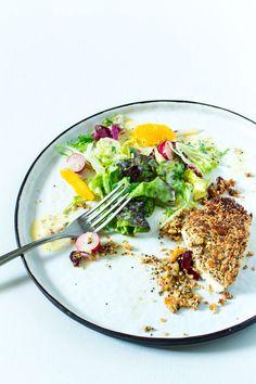 Teller mit Gabel und Salat mit Orangendressing und Müslihähnchen