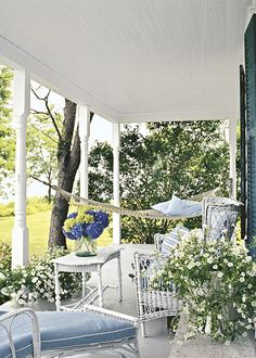 Fresh white porch with comfortable wicker & hammock, blue accents
