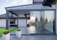 Zadaszenie tarasu - pergole z proszkowo malowanego aluminium, na których zamocowano rozkładany dach z odpornego na wodę, trudno zapalnego włókna