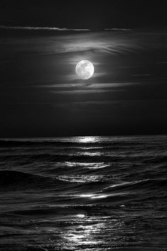 Moody black and white photo of the moon over the sea.
