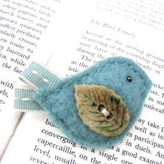 A quirky handmade little birdie brooch to brighten your wardrobe!!  <strong> </strong> Designed and handmade by us in our Dorset studio. For this popular little bird we have used the finest merino woolfelt . It's tail is made from cotton ribbon with embroidery detail and the wing is embellished with a gorgeous handmade ceramic button. This birdie would love to perch onto your wintercoat, cardigan, jacket, the choice is yours. It comes presented on a pretty handmade giftcard and would make an ...