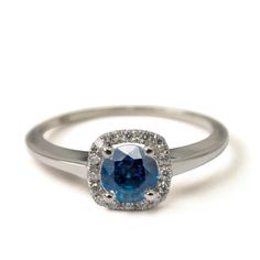 A handmade 14K gold ring set with a blue sapphire and a halo setting.  The center sapphire is surrounded with 17, 1mm diamonds.  The width of