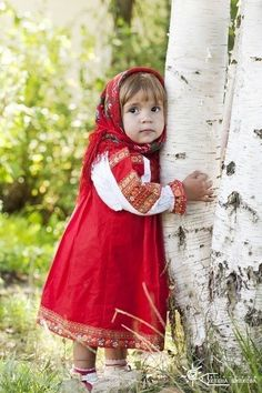 A darling little Russian girl in vibrant ruby hued traditional costume.