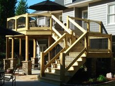 This picture shows a well planned and designed back yard deck with extra features (metal balusters, rock pillars, & arched treatments) which add further appeal to an already appealing gardenscape.