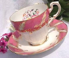 A passion pink, gold and white Paragon tea cup and Saucer. Fine bone china. Made in England. Pattern number: F104J Makers mark: F Circa 1960s.  A hot pink, passionate pink band on white tea cup and saucer. With an intricate gold laurel design overlaying the 1 pink band. Exquisite detail with a beautiful pink and yellow floral bouquet on both cup and saucer. Gold gild on softly scalloped edges. Soft curvature to the cups shape giving added dimension.  No chips, no cracks, no crazing. Cup…