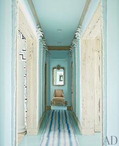 """Place a mirror at the end of your hallway, to avoid the dreaded """"dead-end."""" #turquoise #beachhouse #white #wash #hardwood #doorframe"""