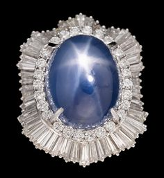 JEWELRY & WATCHES - SALE 1491 - LOT 168 - FREEMAN'S AUCTIONEERS - A star sapphire, diamond and platinum ring-pendant ring is convertible to pendant, centering one star sapphire; weighing approximately: 48.50 carats, surrounded by baguette and round brilliant-cut diamonds; total diamond weight approximately: 7.70 carats, ring-dant findings are in white gold.