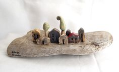 Miniature ceramic houses in white, yellow and brown, on a piece of natural wood.