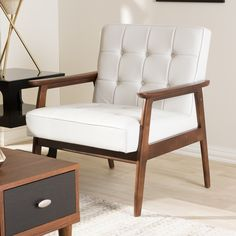 Relax with a refreshing cup of tea in this Stratham white midcentury club chair. Its solid dark wood stained frame is a stark contrast to its button-tufted white faux leather seat that adds a touch of