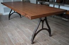 Industrial design table with cast iron legs as a base and a tabletop of cork and walnut . Please take a look at our website for more tables, pictures and info