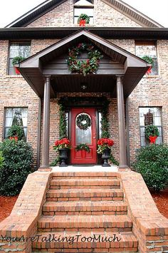 Front porch Christmas decorations with wreaths in each window and garland around front door.
