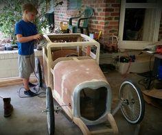A boy working on his soapbox racer. Soap Box Derby Cars, Soap Box Cars, Kids Go Cart, Homemade Go Kart, Kids Play Equipment, Cool Car Drawings, Diy Go Kart, E Motor, Rockabilly Cars