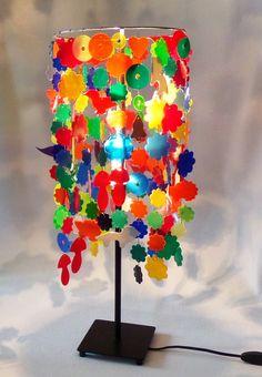 Der Lampenschirm der Tischlampe wurde aus Vinyl Color Schallplatten angefertigt, sie besteht aus ca fast 300 Blüten und Figuren, Durchmesser des Schirmes 23 cm, Gesamthöhe der Lampe 59 cm. Die...