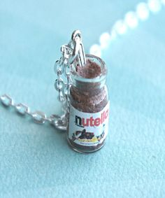 This necklace features a miniature glass jar of Nutella spread along with a croissant charm. The Nutella spread is made from some liquid polymer clay. Both charms are attached to a silver tone necklac
