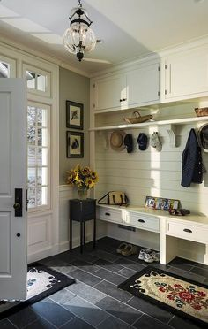 Mudroom-like foyer that is still beautiful in a luxury home.  Also like the sage paint on the wall.