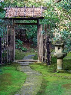 Rustic Japanese Garden gate with lantern beside the path leading into a hidden area where plants can thrive in shade, or maybe there is a koi pond or shishi odoshi.