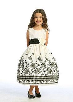 Darling Ivory and Black Floral Taffeta Flower Girl Dress: This elegant ivory floral accented flower girl dress features a taffeta fabric with a beautiful flocked design in black on the lower half of the skirt. The black waistline is embellished with a large detachable flower that can also be worn in the hair. This dress also has a adjustable sash tie back and additional netting underneath for a more volume skirt. Whether she is a flower girl at the upcoming wedding or attending a special…