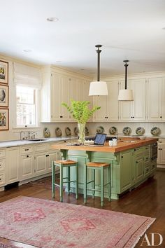 The cabinetry in designer Timothy Corrigan's Los Angeles kitchen is awash in Farrow & Ball paint in shades of white and green | archdigest.com